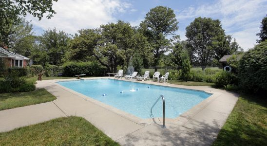 Swimming pool in suburban home with golf course view. poolside patio